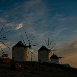 Un hombre camina por los antiguos molinos en la isla griega de Mykonos, en las Cícladas, el 12 de mayo de 2020. - En Mykonos, al comienzo de la temporada turística, la imagen es sorprendente: la elegante isla tradicionalmente llena de extranjeros adinerados se ha convertido en un isla fantasma, que ofrece a los visitantes callejones desiertos, tiendas cerradas, restaurantes y hoteles abandonados. (Foto por ARIS MESSINIS / AFP) | Foto:AFP