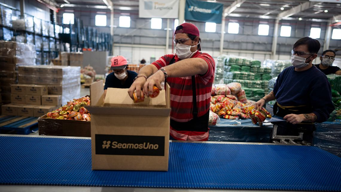 "Workers put together food boxes for the ""Seamos Uno,"" or ""Let's Be One,"" project in Buenos Aires, Argentina, Wednesday, May 13, 2020."