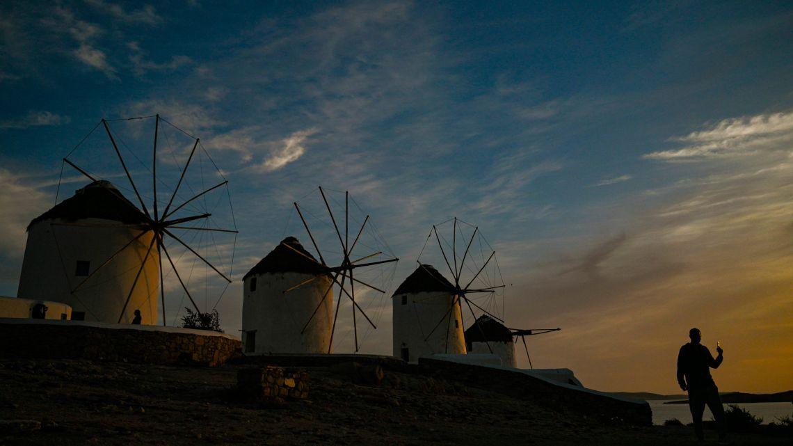 Un hombre camina por los antiguos molinos en la isla griega de Mykonos, en las Cícladas, el 12 de mayo de 2020. - En Mykonos, al comienzo de la temporada turística, la imagen es sorprendente: la elegante isla tradicionalmente llena de extranjeros adinerados se ha convertido en un isla fantasma, que ofrece a los visitantes callejones desiertos, tiendas cerradas, restaurantes y hoteles abandonados. (Foto por ARIS MESSINIS / AFP)   Foto:AFP