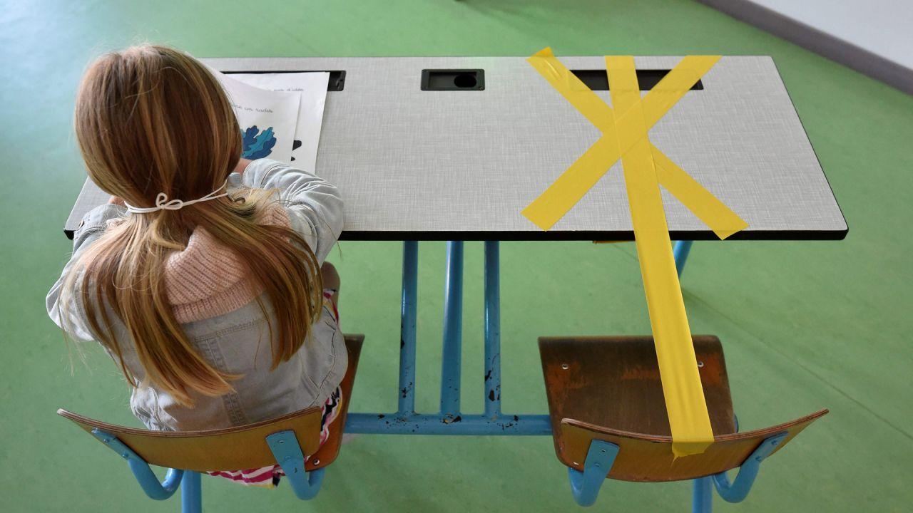 Una alumna de la escuela primaria Sainte-Croix trabaja mientras la mitad de su escritorio está marcada con una cinta adhesiva para garantizar que se mantenga una distancia segura el 15 de mayo de 2020 en Hannut, ya que el bloqueo se introdujo hace dos meses para luchar contra la propagación del Covid La enfermedad causada por el nuevo coronavirus se está aliviando progresivamente. (Foto por JOHN THYS / AFP) | Foto:AFP