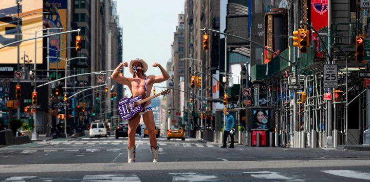 El artista callejero Robert John Burck, conocido como The Naked Cowboy, posa en Times Square el 15 de mayo de 2020 en la ciudad de Nueva York. - Las medidas de bloqueo pandémico en la ciudad de Nueva York se han extendido hasta el 13 de junio bajo una orden ejecutiva firmada por el gobernador estatal Andrew Cuomo a fines del 14 de mayo de 2020. Sin embargo, las órdenes de quedarse en casa se facilitarán para las cinco regiones menos pobladas del estado, sin embargo, permitiendo negocios allí para volver a trabajar gradualmente. (Foto de Johannes EISELE / AFP))