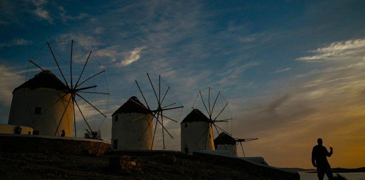 Un hombre camina por los antiguos molinos en la isla griega de Mykonos, en las Cícladas, el 12 de mayo de 2020. - En Mykonos, al comienzo de la temporada turística, la imagen es sorprendente: la elegante isla tradicionalmente llena de extranjeros adinerados se ha convertido en un isla fantasma, que ofrece a los visitantes callejones desiertos, tiendas cerradas, restaurantes y hoteles abandonados. (Foto por ARIS MESSINIS / AFP)