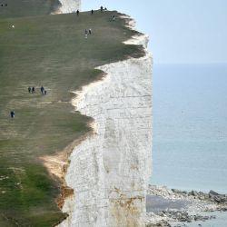 La gente camina por el acantilado sobre el faro en Beachy Head, cerca de Eastbourne, en la costa sur de Inglaterra, el 17 de mayo de 2020, después de una flexibilización de las reglas de bloqueo en Inglaterra durante la nueva pandemia de coronavirus COVID-19. - Se les pide a las personas que  | Foto:AFP