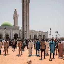 Los fieles musulmanes son vistos durante las oraciones del viernes en la Mezquita de los Mourides, que abre sus primeras oraciones del viernes después de dos meses en Dakar el 15 de mayo de 2020. Esto se produce después de que el presidente de Senegal, Macky Sall, relajó las medidas para combatir el COVID. 19 coronavirus por lugares de culto, aunque algunas mezquitas decidieron permanecer cerradas debido al aumento de los casos de coronavirus COVID-19 en Senegal. (Foto por JOHN WESSELS / AFP) | Foto:AFP