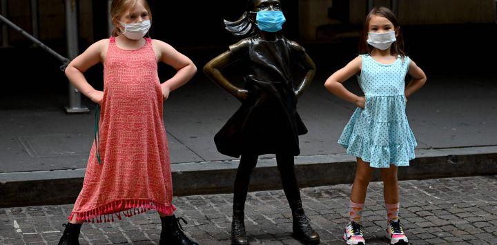 Dos jóvenes posan junto a la escultura de bronce enmascarada de la