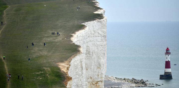 La gente camina por el acantilado sobre el faro en Beachy Head, cerca de Eastbourne, en la costa sur de Inglaterra, el 17 de mayo de 2020, después de una flexibilización de las reglas de bloqueo en Inglaterra durante la nueva pandemia de coronavirus COVID-19. - Se les pide a las personas que