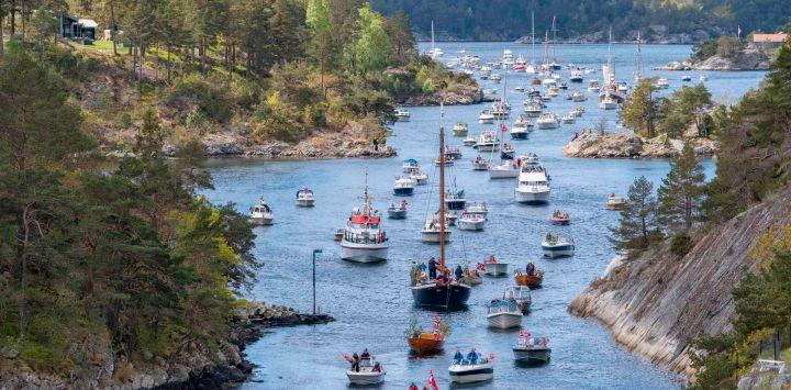 Los barcos desfilan en la vía fluvial de Blindleia en Lillesand, sur de Noruega, durante las celebraciones del Día de la Constitución el 17 de mayo de 2020. - La fiesta se celebra de una manera nueva y diferente este año debido al nuevo coronavirus. (Foto por Tor Erik SCHRODER / NTB Scanpix / AFP) / Noruega OUT