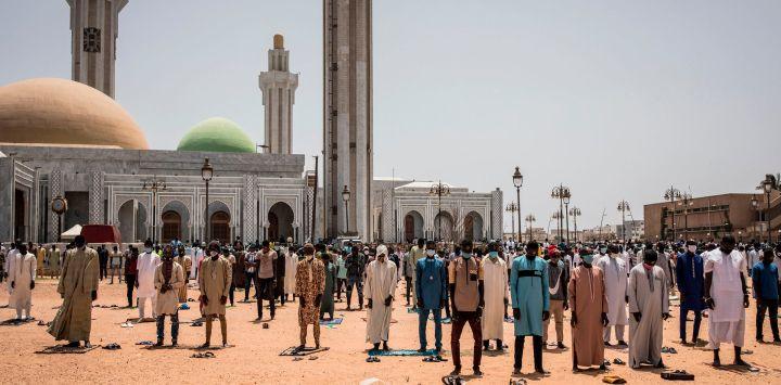 Los fieles musulmanes son vistos durante las oraciones del viernes en la Mezquita de los Mourides, que abre sus primeras oraciones del viernes después de dos meses en Dakar el 15 de mayo de 2020. Esto se produce después de que el presidente de Senegal, Macky Sall, relajó las medidas para combatir el COVID. 19 coronavirus por lugares de culto, aunque algunas mezquitas decidieron permanecer cerradas debido al aumento de los casos de coronavirus COVID-19 en Senegal. (Foto por JOHN WESSELS / AFP)