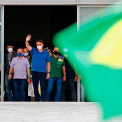 El presidente brasileño, Jair Bolsonaro (C), saluda a los partidarios durante una manifestación en Brasilia el 17 de mayo de 2020, en medio de la nueva pandemia de coronavirus. - El número de muertos en Brasil COVID-19 superó los 15,000 el sábado, según datos oficiales, mientras que su número de infecciones superó los 230,000, lo que lo convierte en el país con el cuarto número más alto de casos en el mundo. (Foto por Sergio LIMA / AFP) | Foto:AFP