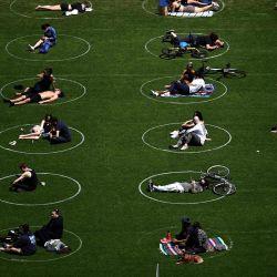 Se ve a personas practicando distanciamiento social en círculos blancos en Domino Park, durante la pandemia de Covid-19 el 17 de mayo de 2020 en el distrito de Brooklyn de la ciudad de Nueva York. (Foto de Johannes EISELE / AFP) | Foto:AFP