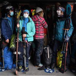 Los alpinistas con máscaras faciales abordan un teleférico hasta el pico 'Aiguille du Midi' en Chamonix, el 16 de mayo de 2020, el primer día de su reapertura, mientras Francia alivia las medidas de bloqueo tomadas para frenar la propagación de la pandemia COVID-19, causada por el nuevo coronavirus. (Foto por PHILIPPE DESMAZES / AFP) | Foto:AFP