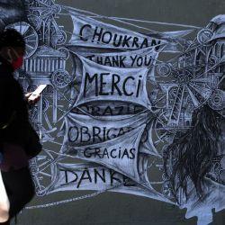 Una mujer que llevaba una máscara protectora pasa junto a una pegada del artista callejero francés Ardif en París, que representa a una Marianne y a un miembro del personal médico como un homenaje para agradecer a los cuidadores, el 15 de mayo de 2020, mientras Francia facilita las medidas de cierre. tomado para frenar la propagación del COVID-19, (el nuevo coronavirus). (Foto por JOEL SAGET / AFP) | Foto:AFP