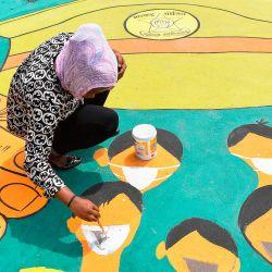 Un artista pinta un mural de piso dedicado a las fuerzas policiales para agradecer a su servicio desafiando todos los riesgos durante un bloqueo nacional para combatir la propagación del coronavirus COVID-19, en Mumbai el 16 de mayo de 2020. (Foto por INDRANIL MUKHERJEE / AFP) | Foto:AFP