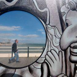 Las personas que caminan a lo largo del paseo marítimo se ven a través del agujero de una atracción de fotografía en Worthing, sur de Inglaterra, el 16 de mayo de 2020, después de una flexibilización de las reglas de bloqueo en Inglaterra durante la nueva pandemia de coronavirus COVID-19. - Se les pide a las personas que  | Foto:AFP