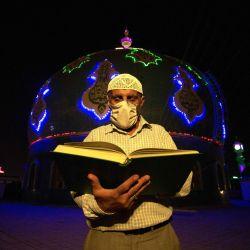 Un hombre musulmán iraquí lee el Corán en 'Lailat al Qardr' o la 'noche del destino' que durante el mes sagrado del Ramadán marca la noche en que el Corán se reveló por primera vez al profeta Mahoma, frente a la gran mezquita de Musawi en el Basora, en el sur de la ciudad iraquí, en medio de la nueva pandemia de coronavirus, a principios del 17 de mayo de 2020. (Foto de Hussein FALEH / AFP) | Foto:AFP