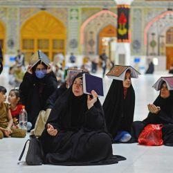 Los musulmanes chiítas se reúnen, aunque en menor número debido a la pandemia de COVID-19, en el santuario Imam Ali en la ciudad sagrada iraquí central de Najaf a fines del 16 de mayo de 2020, para conmemorar a Lailat al-Qadr, una noche en el mes sagrado de Ramadán durante el cual el Corán fue revelado por primera vez al profeta Mahoma en el siglo VII. - Los fieles colocaron copias del Corán en sus cabezas para transmitir veneración durante las oraciones de la noche a la mañana en un ritual de siglos de antigüedad, mientras le suplicaban a Dios que los librara de la nueva pandemia de coronavirus. (Foto por Haidar HAMDANI / AFP) | Foto:AFP