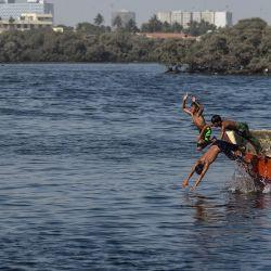 Los jóvenes saltan de un bote mientras disfrutan de nadar en el agua del Mar Arábigo en Karachi el 17 de mayo de 2020. (Foto de Asif HASSAN / AFP) | Foto:AFP