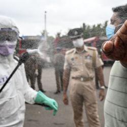 Un oficial de policía (L) rocía desinfectante sobre un hombre antes de abordar un autobús especial organizado por la policía de Sri Lanka para transportar a los ciudadanos varados de regreso a sus ciudades de origen después de que el gobierno puso fin a un bloqueo que se impuso como medida preventiva contra el coronavirus COVID-19, en un terreno público en Kalutara a unos 43 km de Colombo el 16 de mayo de 2020. (Foto de LAKRUWAN WANNIARACHCHI / AFP) | Foto:AFP