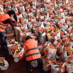 Los voluntarios preparan bolsas que contienen comida gratis para distribuir a los necesitados en Ginebra el 16 de mayo de 2020, mientras la pandemia de COVID-19 pone de relieve a los pobres, generalmente invisibles, de Ginebra, una de las ciudades más caras del mundo. (Foto por Fabrice COFFRINI / AFP) | Foto:AFP