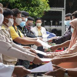 Los funcionarios tailandeses (L) posan mientras entregan certificados a personas autorizadas a dejar una cuarentena de 14 días impuesta para detener la propagación del coronavirus COVID-19 en una escuela en Panaret, en la provincia de Pattani, en el sur de Tailandia, el 17 de mayo de 2020. ( Foto de Tuwaedaniya MERINGING / AFP) | Foto:AFP