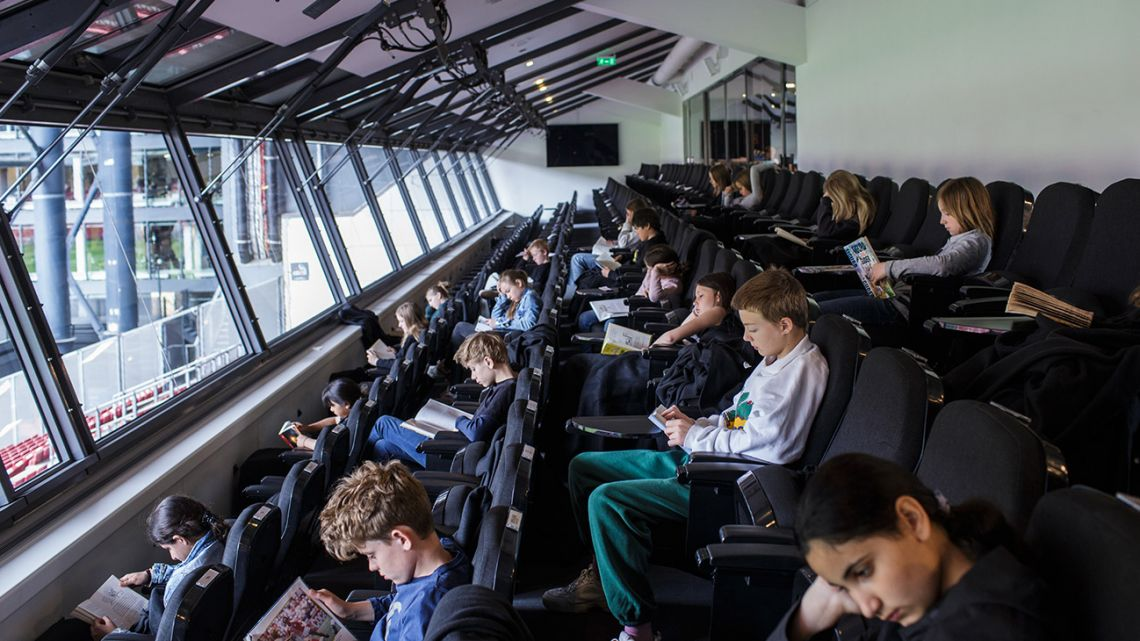 Children attend a class held in the high class tribune at the Telia Parken stadium in order to keep the social distances amid the new coronavirus pandemic on May 15, 2020 in Copenhagen. Denmark was the first country in Europe to reopen its schools for the youngest pupils on April 15. In addition to practising social distancing and regular handwashing, classes must be held outdoors as much as possible to limit the spread of the virus.