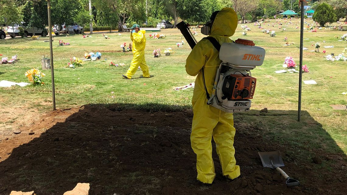 "A gravedigger, wearing personal protective equipment to prevent the spread of the new coronavirus, Covid-19, disinfects after a burrial at the ""Jardínes del Recuerdo"" Cemetery, in Managua on May 15, 2020. Nicaraguan residents and doctors fear that the country reaching a ""chaotic situation"" due to the fast spread of COVID-19, without measures to contain the pandemic and aggravated by official secrecy over those affected."