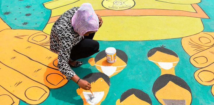 Un artista pinta un mural de piso dedicado a las fuerzas policiales para agradecer a su servicio desafiando todos los riesgos durante un bloqueo nacional para combatir la propagación del coronavirus COVID-19, en Mumbai el 16 de mayo de 2020. (Foto por INDRANIL MUKHERJEE / AFP)