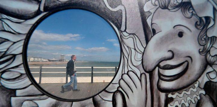 Las personas que caminan a lo largo del paseo marítimo se ven a través del agujero de una atracción de fotografía en Worthing, sur de Inglaterra, el 16 de mayo de 2020, después de una flexibilización de las reglas de bloqueo en Inglaterra durante la nueva pandemia de coronavirus COVID-19. - Se les pide a las personas que