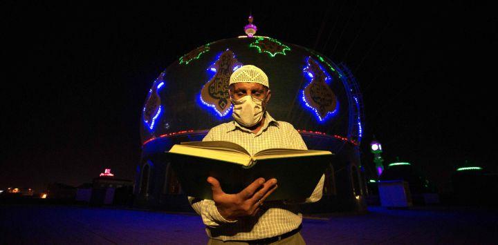 Un hombre musulmán iraquí lee el Corán en 'Lailat al Qardr' o la 'noche del destino' que durante el mes sagrado del Ramadán marca la noche en que el Corán se reveló por primera vez al profeta Mahoma, frente a la gran mezquita de Musawi en el Basora, en el sur de la ciudad iraquí, en medio de la nueva pandemia de coronavirus, a principios del 17 de mayo de 2020. (Foto de Hussein FALEH / AFP)