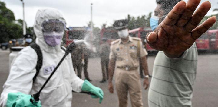 Un oficial de policía (L) rocía desinfectante sobre un hombre antes de abordar un autobús especial organizado por la policía de Sri Lanka para transportar a los ciudadanos varados de regreso a sus ciudades de origen después de que el gobierno puso fin a un bloqueo que se impuso como medida preventiva contra el coronavirus COVID-19, en un terreno público en Kalutara a unos 43 km de Colombo el 16 de mayo de 2020. (Foto de LAKRUWAN WANNIARACHCHI / AFP)
