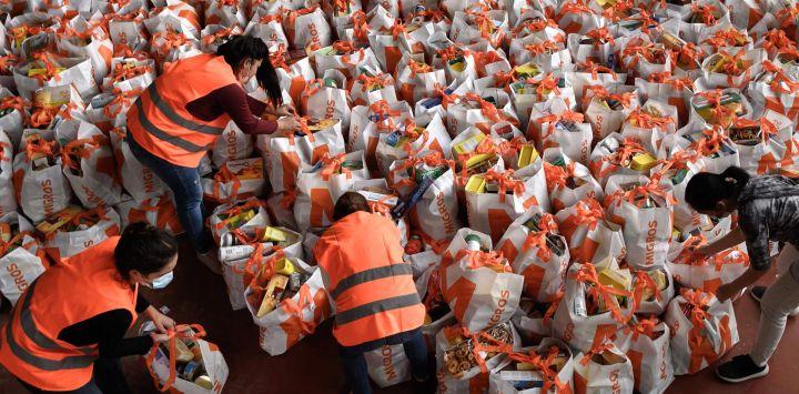Los voluntarios preparan bolsas que contienen comida gratis para distribuir a los necesitados en Ginebra el 16 de mayo de 2020, mientras la pandemia de COVID-19 pone de relieve a los pobres, generalmente invisibles, de Ginebra, una de las ciudades más caras del mundo. (Foto por Fabrice COFFRINI / AFP)