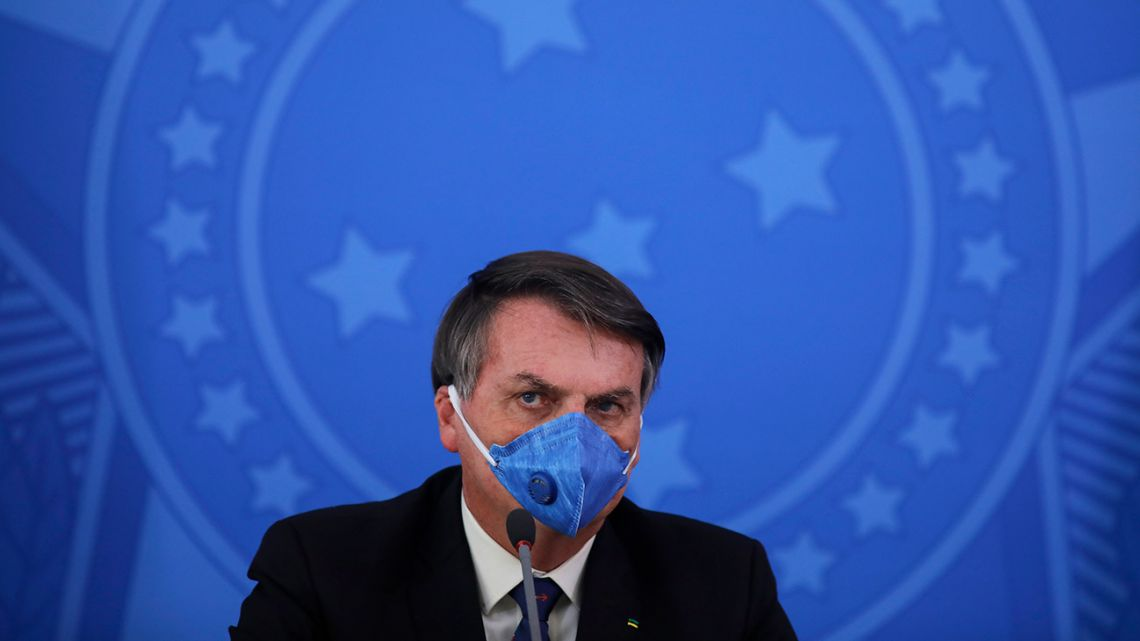 Brazil's President Jair Bolsonaro wears a face mask during a press conference on the coronavirus pandemic COVID-19 at the Planalto Palace in Brasilia, Brazil on March 20, 2020.