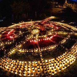Gertrud Schop, de 60 años, enciende velas dispuestas en forma de cruz, con una vela dedicada a cada una de las más de 8,000 víctimas alemanas relacionadas con Covid-19, en Zella-Mehlis, Alemania oriental, el 19 de mayo de 2020, en medio la nueva pandemia de coronavirus / COVID-19. - Schop planea continuar el proyecto hasta que esté disponible una vacuna contra Covid-19. (Foto por JENS SCHLUETER / AFP) | Foto:AFP