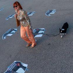 Una mujer pasea a su perro a través de las marcas de distanciamiento social después de la protesta del Partido de la Libertad de Austria (FPOe) contra las restricciones del gobierno contra la pandemia de coronavirus en la plaza Helden frente al palacio de Hofburg en Viena, Austria, el 20 de mayo de 2020. (Foto por JOE KLAMAR / AFP) | Foto:AFP