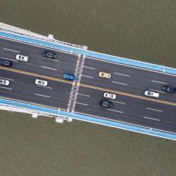 Una foto aérea muestra a los automovilistas que viajan en el puente número dos de Wuhan Changjiang en Wuhan, la provincia central china de Hubei, el 20 de mayo de 2020. - China ha controlado en gran medida el coronavirus dentro de sus fronteras desde que el brote surgió por primera vez en la ciudad de Wuhan a fines del año pasado. . (Foto por Héctor RETAMAL / AFP) | Foto:AFP