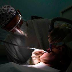 Un dentista que usa equipo de protección trata a un paciente en su clínica dental en Guebwiller, este de Francia, el 20 de mayo de 2020, Francia alivia las medidas de bloqueo tomadas para frenar la propagación de la enfermedad COVID-19 causada por el nuevo coronavirus. (Foto por SEBASTIEN BOZON / AFP)   Foto:AFP