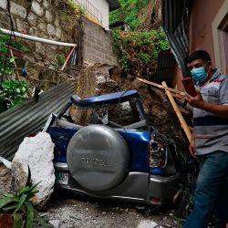 Un hombre se hace una selfie con su automóvil después de que fue aplastado por una roca que cayó de una ladera debido a las fuertes lluvias en Tegucigalpa, el 20 de mayo de 2020. - La temporada de lluvias en Honduras ha dejado considerables pérdidas económicas en los departamentos de Francisco Morazán. y Valle en la última semana. (Foto por ORLANDO SIERRA / AFP) | Foto:AFP
