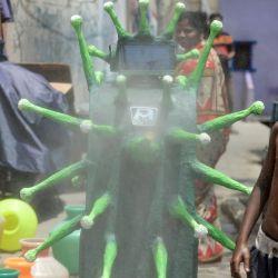 Los residentes observan mientras los funcionarios de salud (no vistos) navegan un robot con temática de coronavirus que rocía desinfectante en un área residencial después de que el gobierno alivió un bloqueo nacional impuesto como medida preventiva contra el coronavirus COVID-19, en Chennai el 20 de mayo de 2020. Foto de Arun SANKAR / AFP) | Foto:AFP
