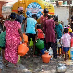 Los residentes llenan contenedores de plástico con agua potable durante una distribución de suministro gratuita organizada por el Gobierno de Telangana de la Junta Metropolitana de Abastecimiento de Agua y Alcantarillado de Hyderabad en un barrio pobre de Secunderabad, la ciudad gemela de Hyderabad el 20 de mayo de 2020. (Foto de NOAH SEELAM / AFP) | Foto:AFP