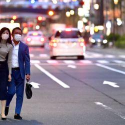Una pareja con máscaras faciales en medio de preocupaciones por el coronavirus COVID-19 busca un taxi en Tokio el 20 de mayo de 2020. - Japón el 14 de mayo levantó un estado de emergencia impuesto debido al coronavirus COVID-19 para la mayoría del país, pero lo mantuvo en su lugar para las principales ciudades de Tokio y Osaka. (Foto por CHARLY TRIBALLEAU / AFP) | Foto:AFP