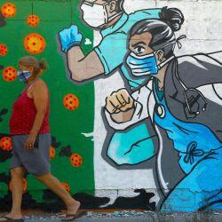 Una mujer pasa junto a un mural relacionado con el coronavirus pintado por el artista Mick Martínez en Ciudad Juárez, estado de Chihuahua, México, el 19 de mayo de 2020. (Foto de HERIKA MARTINEZ / AFP) | Foto:AFP