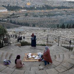 Los palestinos se reúnen para romper su ayuno durante el mes sagrado musulmán del Ramadán, en el Monte de los Olivos con el telón de fondo de la Ciudad Vieja de Jerusalén y el recinto cerrado de la Mezquita al-Aqsa el 19 de mayo de 2020, durante la nueva crisis pandémica de coronavirus. (Foto por Ahmad GHARABLI / AFP) | Foto:AFP