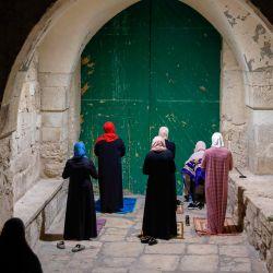 Las adoradoras palestinas musulmanas, distanciadas entre sí debido a la pandemia del coronavirus COVID-19, rezan frente a la puerta cerrada del complejo de la mezquita de Aqsa en la Ciudad Vieja de Jerusalén, mientras marcan el Lailat al-Qadr, una de las noches más santas durante el mes de ayuno musulmán del Ramadán, a finales del 19 de mayo de 2020. - Lailat al-Qadr (Noche del Destino) marca la noche en que los musulmanes creen que los primeros versos del Corán fueron revelados al profeta Mahoma a través del arcángel Gabriel. (Foto por AHMAD GHARABLI / AFP) | Foto:AFP