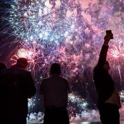 La gente disfruta de los fuegos artificiales que explotan sobre el Bósforo para conmemorar el Día de la Juventud y el Deporte en Estambul el 19 de mayo de 2020 durante un toque de queda de cuatro días destinado a frenar la propagación de la pandemia COVID-19, causada por el nuevo coronavirus. (Foto por Ozan KOSE / AFP) | Foto:AFP