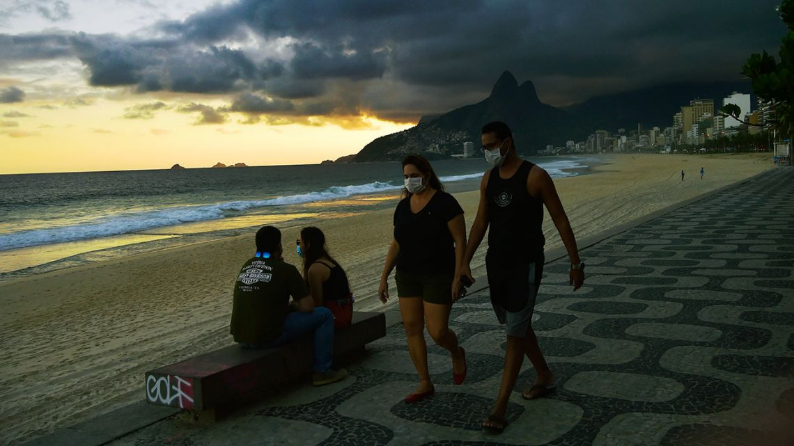 People wear face masks as they walk along Ipanema Beach in Rio de Janeiro on May 19, 2020.