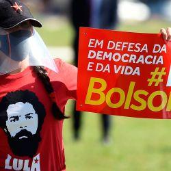 Activistas de la oposición brasileña participan en una protesta contra el presidente brasileño Jair Bolsonaro, en medio de la pandemia de corovavirus COVID-19, frente al Congreso Nacional en Brasilia, el 21 de mayo de 2020. - Los partidos de la oposición brasileña presentaron una solicitud de juicio político contra Bolsonaro en el Bajo Casa. (Foto de EVARISTO SA / AFP)   Foto:AFP