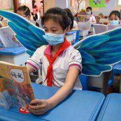 Esta foto tomada el 20 de mayo de 2020 muestra a estudiantes de primaria usando alas para mantener el distanciamiento social en medio de las preocupaciones por el coronavirus COVID-19, en un aula en Taiyuan, en la provincia de Shanxi, en el norte de China. (Foto por STR / AFP) / China OUT   Foto:AFP