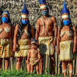 Los indígenas colombianos Huitoto posan con máscaras faciales, en medio de las preocupaciones por el coronavirus COVID-19, en Leticia, departamento de Amazonas, Colombia, el 20 de mayo de 2020. (Foto de Tatiana de Nevó / AFP)   Foto:AFP