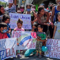 Los migrantes venezolanos que desean regresar a su país debido a la nueva pandemia de coronavirus, sostienen carteles durante una protesta frente a la terminal de autobuses en Medellín, Colombia, en demanda de la oportunidad de subir a un autobús para llevarlos a la frontera, el 20 de mayo. 2020. (Foto de JOAQUIN SARMIENTO / AFP)   Foto:AFP