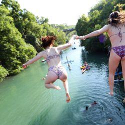 Los residentes saltan de un puente mientras nadan, reman y practican kayak en Barton Creek el 20 de mayo de 2020 en Austin, Texas. El gobernador de Texas, Greg Abbott, anunció que los bares, salas de degustación de vinos, boleras, pistas de patinaje, salas de bingo, acuarios y eventos ecuestres se abrirán el viernes 22 de mayo a pesar de un aumento en los casos confirmados de coronavirus (COVID-19) en el estado. Tom Pennington / Getty Images / AFP   Foto:AFP